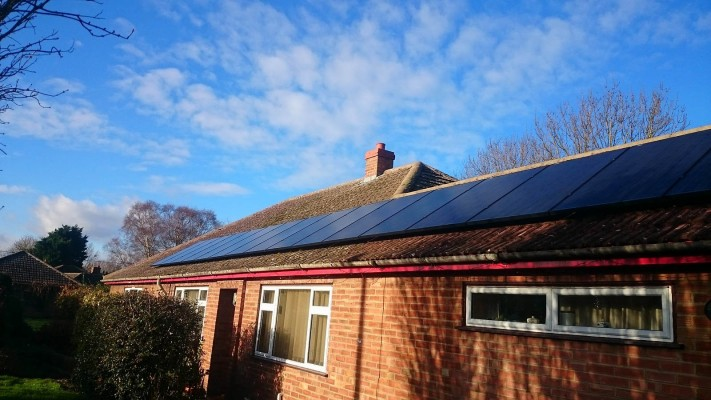 One long row of solar panels installed on top of a bungalow house near Cambridge