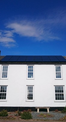 Large renovated house with sixteen solar panels producing electricity for a family living near Cambridge
